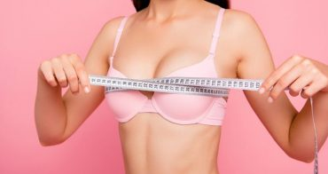 Cropped close-up photo of nice cute adorable attractive cheerful positive optimistic girl in beige bra measuring chest size line with tape isolated over pink background